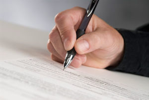 Man's Hand Holding a Nice Pen and Signing Paperwork
