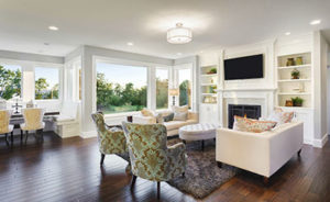Luxury Living Room With Upholstered Chairs, Large Windows, Built-In Shelving and a TV Mounted Over a Fireplace