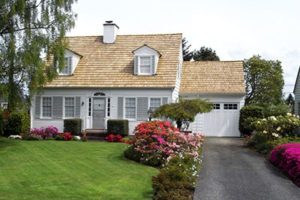 Pretty Home With Tan Roof and White Siding Sits Under a Tree With a Beautifully Landscaped Yard and Asphalt Driveway