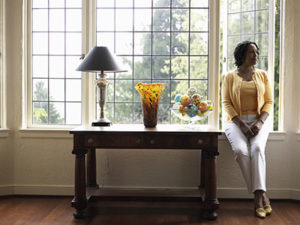 Well-Dressed Woman Sits on the Sill of Her Home's Large Windows, a Wooden Table Next to Her With a Lamp, Vase and Decorative Bowl