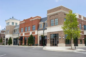 Brick and Stone Two-Story Storefronts Line a Clean Quiet Street With Parking Spaced and Trees Along the Sidewalk