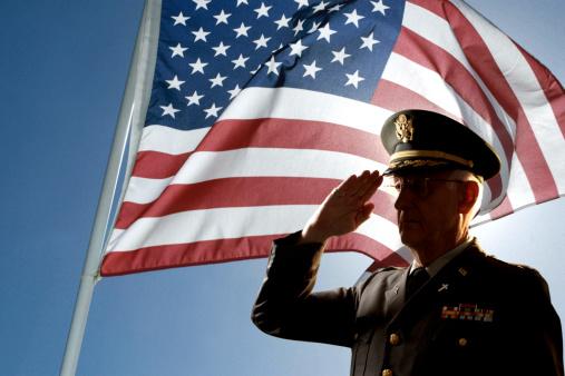 Servicemen saluting the flag