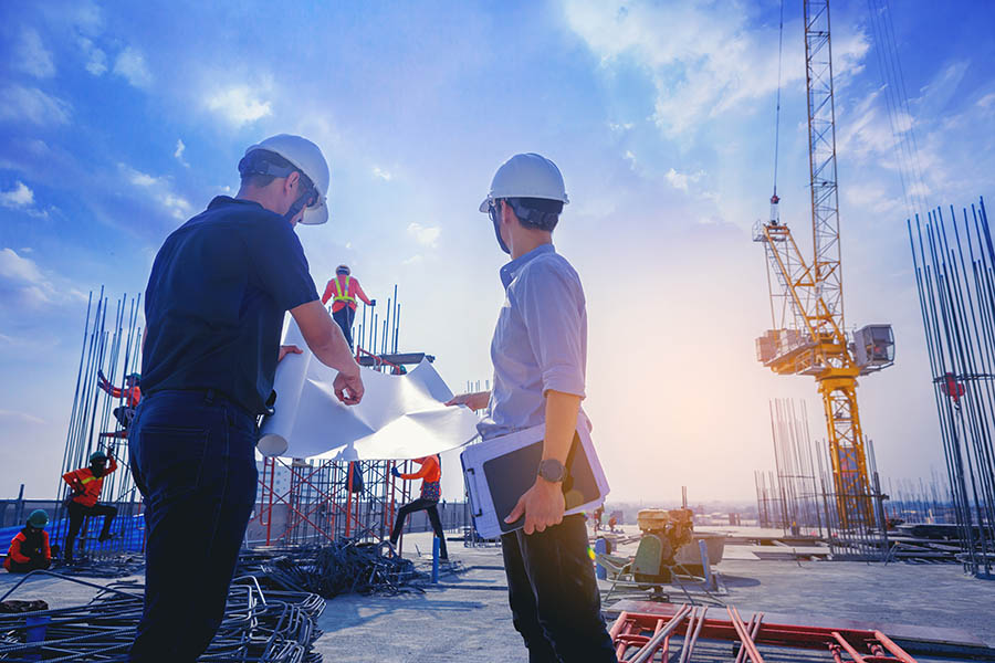 Specialized Business Insurance - Contractor and Foreman Discuss Plans Over Blueprints at a Job Site With Heavy Equipment and Materials