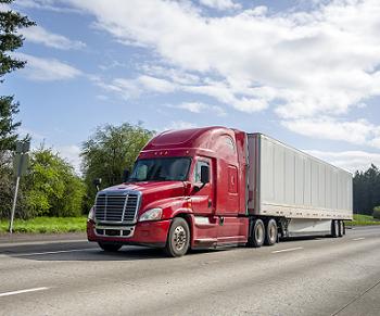 Red semi truck driving down a freeway
